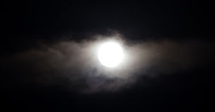 The moon in the haze of the clouds at night.  Royalty Free Stock Photos