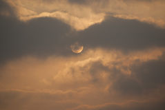 Moon hidden behind  clouds in the evening Royalty Free Stock Photography