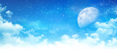 Moon light in a cloudy blue sky. Blue sky background, moon light in white clouds, bright stars shining behind Royalty Free Stock Image