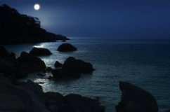 The moon lights the sea rocky coast. Sea and rocky shore under t. He moonlight. Beautiful night seascape royalty free stock photo