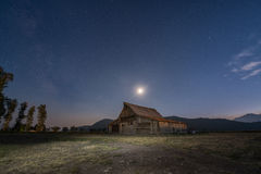 Moon and Milky Way over Moulton Barn. One of the historic Moulton Barns under the night sky Stock Photography