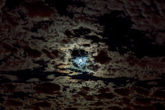Moon in the night sky. Clouds and stars above them. Royalty Free Stock Photography