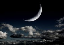 The moon in the night sky. In clouds Royalty Free Stock Images