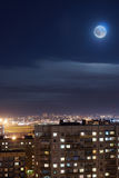 The moon in the night sky over the city block Royalty Free Stock Photos