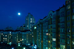 Moon in the night sky over city. Royalty Free Stock Images