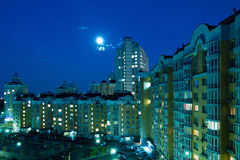 Moon in the night sky over city. Stock Photography