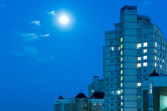 Moon in the night sky over city. Royalty Free Stock Photography