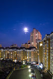 Moon in the night sky over city. Royalty Free Stock Image