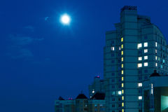 Moon in the night sky over city. Royalty Free Stock Photo