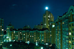 Moon in the night sky over city. Stock Images