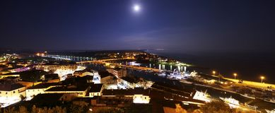 Moon and night view on the city  `Castiglione della Pescaia`. royalty free stock photography