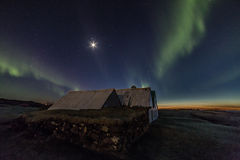 Northern Lights. The moon and the northern lights or Aurora Borealis invade the skies and the sun sets over a farm in Iceland Royalty Free Stock Image