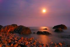 Moon o trajeto sobre o mar da noite com rochas Imagem de Stock