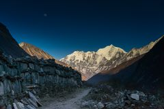 Langtang valley moonrise over mountain. Moon and old wall ruin in Nepal trek Stock Photography