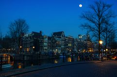 Moon over Amsterdam, Netherlands canals and. Full moon over Amsterdam, Netherlands canals and bridges. Night view of Keizersgracht and famous touristic place Stock Image