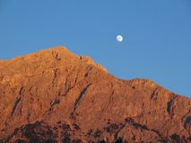 Moon over barren mountain Royalty Free Stock Image