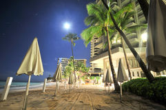 Moon over beach with umbrella's and trees Royalty Free Stock Photography