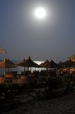 Moon over beach umbrellas. And tables by the ocean at night stock image