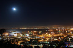 Moon over Cape Town Harbor. A nighttime view overlooking Cape Town, South Africa, with moonlight reflecting from the harbor waters Stock Photos