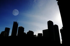 Moon over the city. An image of early morning over a city skyline with a moon stock photo
