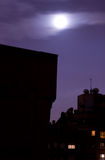 Moon over city skyline. Blurred moon over a cold night sky royalty free stock images