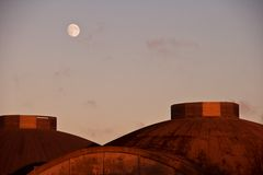 Moon over domed roofs. A view of a shiny moon as it appears over metal domed roofs at sunset Royalty Free Stock Photo