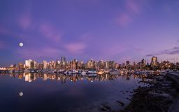 Moon over Downtown Vancouver at sunset from Stanley Park. royalty free stock photography