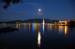 Moon Over Geneva. Geneva lake front by moonlight with the city lights and the Jet d'Eau Royalty Free Stock Photos