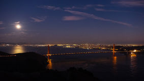 Moon over Golden Gate Bridge, San Francisco, California. Moon in night sky over Golden Gate Bridge illuminated at night in San Francisco, California Royalty Free Stock Images