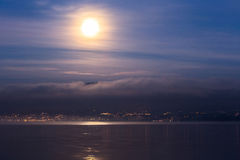 Moon Over Jura Mountain, Swiss. Full moon over Jura mountain range and Lake Geneva in a winter dawn Royalty Free Stock Image