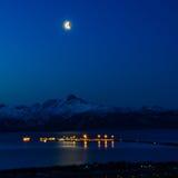 Moon over Kachemak Bay. Moon shines down over the lights of the Homer Spit in Kachemak Bay Alaska Royalty Free Stock Image