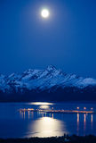 Moon Over the Kenai. Moon reflects off Kachemak Bay with the lights of the Homer Spit glowing in the distance Royalty Free Stock Photo