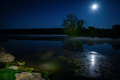 Moon over lake. Scenic nighttime landscape with full moon rising over the lake stock image
