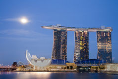 Moon over Marina Bay Sands. Night shot of moon over Marina Bay Sands Hotel and Integrated Resort, The Helix Bridge, and the Singapore Arts and Science Museum Royalty Free Stock Images