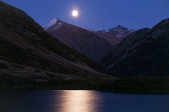 Moon over mountain lakes and lunar path. Stock Photos