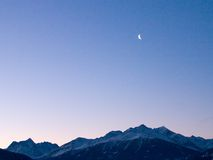 The moon over the mountains. A nice crescent of the moon in a blue/rose sky at sunset over the swiss mountains Royalty Free Stock Photography