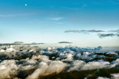 Moon over the mountains covered in clouds Stock Photos