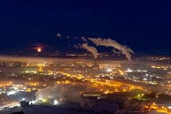 Moon over night industrial city, Norilsk stock image