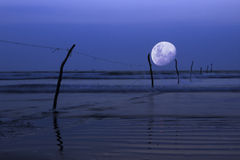 Moon over ocean, night scene. A blue moon over blue night scene and a slow dreamy ocean with fishing net poles in the ocean going deep into the ocean, half moon Stock Photo