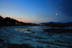 Moon over picturesque beach. Scenic view of moonlight beach in Lodingen, Nordland, Norway Royalty Free Stock Image