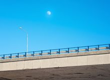 Moon over road bridge in beautiful sunny day. Urban highway bridge with lamp and blue sky royalty free stock image