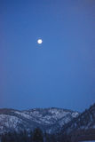 Moon over Rocky Mountain Winter Mountains, Montana Royalty Free Stock Image