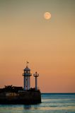 Moon over the sea. And a beacon Royalty Free Stock Photography