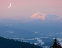 Moon over snow-covered peak Stock Image