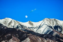 Moon Over Snowcapped Mountain Stock Photos