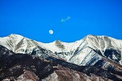 Moon Over Snowcapped Mountain Stock Photos
