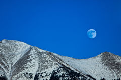 Moon Over Snowcapped Mountain. Colorado, USA stock images