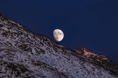 Moon over snowy mountain in Switzerland Stock Photos
