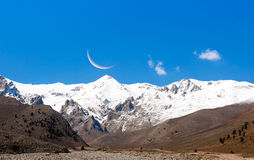 Moon over snowy mountains Royalty Free Stock Photos
