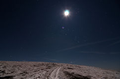 Moon over snowy path. Moon shining over snowy path Royalty Free Stock Image